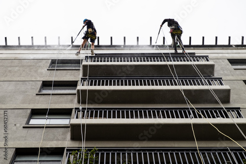Two male window cleaners abseiling down apartment exterior Canvas Print