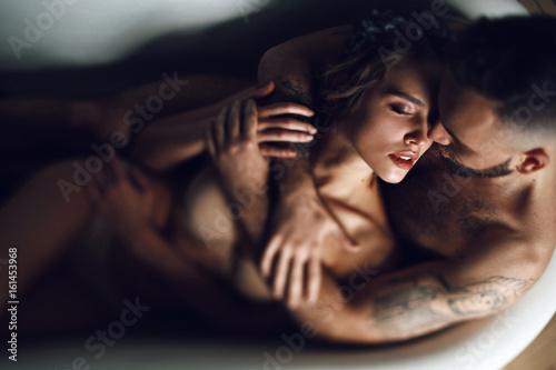 Fotografia  Man hugs woman from behind lying in the bath
