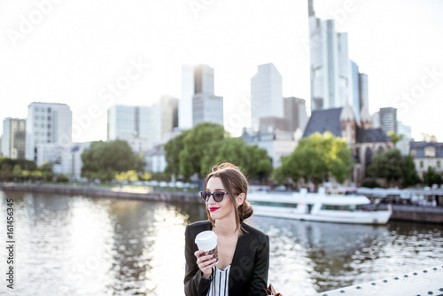 Photo Young businesswoman having a coffee break outdoors sitting on the bridge in Fran