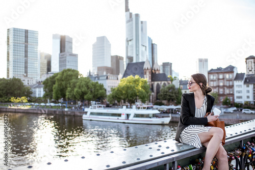 Young businesswoman having a coffee break outdoors sitting on the bridge in Fran Wallpaper Mural