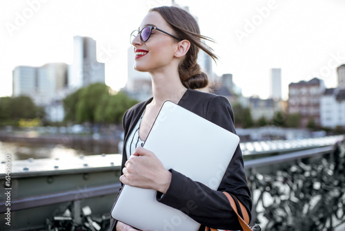 fototapeta na drzwi i meble Portrait of a young businesswoman with laptop standing on the bridge in Frankfurt city