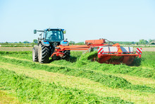 Tractor With Hay Mower Cutting Grass For Hay On A Field.
