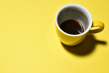 Yellow Half Drinked Cup Of Coffee On Paper Background