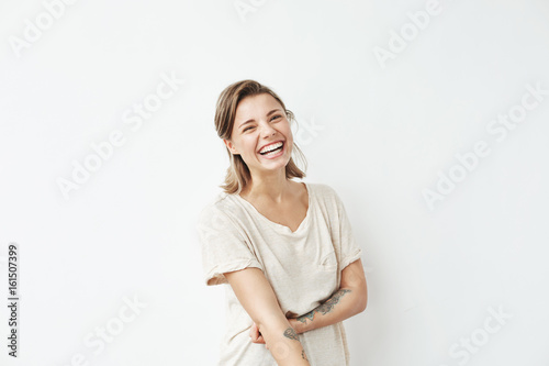 Fotografie, Tablou  Cheerful happy young beautiful girl looking at camera smiling laughing over white background