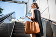 canvas print picture - Young businesswoman with bag and phone getting up on the escalator during the business trip in the modern city