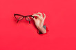 canvas print picture - Female hand in paper hole with glasses