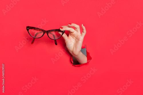 Photo  Female hand in paper hole with glasses
