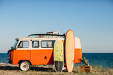 bus with a surfboard on the roof is a parked near the beach - 161535378