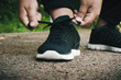 Athlete ties up shoelaces on sneakers before training in the open air