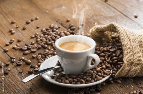 filizanka-kawy-z-talerzykiem-i-lyzeczka-na-stole-obok-ziarna-rozsypane-z-worka
