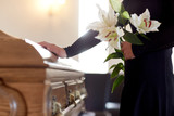 Fototapeta Kwiaty - woman with lily flowers and coffin at funeral
