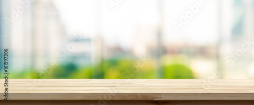 Obraz Wood table top on blur  city building view background looking through glass window, panoramic banner - fototapety do salonu