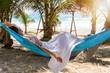Junge Frau in weißem Kleid entspannt auf einer Hängematte am tropischen Strand unter Palmen