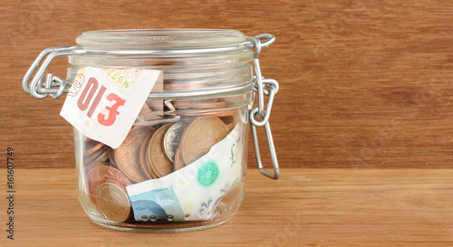 Glass jar filled with cash savings on a wood background Canvas Print