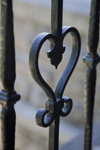 Heart Shaped Wrought Iron Against A Blurry Background.