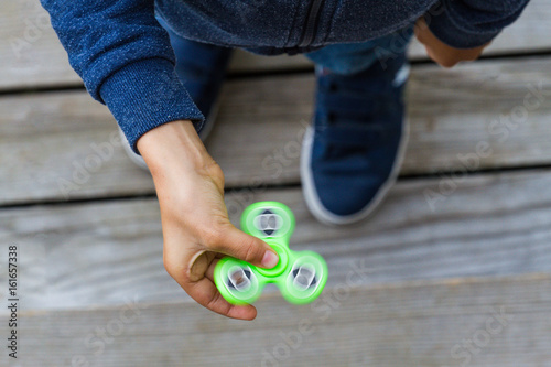 Obraz na plátně Kid playing with popular fidget spinner toy. Top view