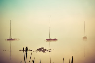 Fototapeta Minimalistyczny Morning foggy lake landscape. Boats on the lake.