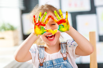 Fototapeta funny child girl draws laughing shows hands dirty with paint