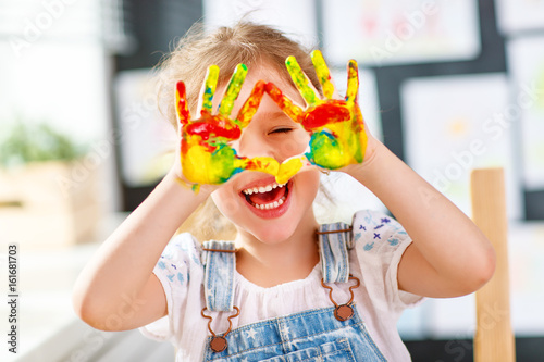 Photo  funny child girl draws laughing shows hands dirty with paint