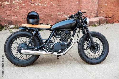 Foto Black vintage custom motorcycle motorbike cafe racer with black full face helmet in front of brick wall