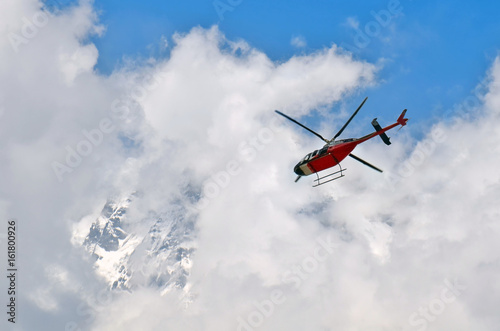 Tuinposter Helicopter Helicopter in the cloudy sky and mountain. Himalayan Mountains, Annapurna National Park.
