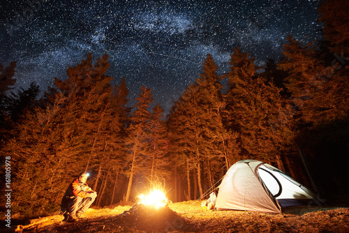 Fototapeta Male tourist have a rest in his camp near the forest at night. Man sitting near campfire and tent under beautiful night sky full of stars and milky way, and enjoying night scene obraz na płótnie