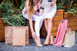 Portrait of two young attractive women who sit with shopping bags and one of them trying on shoes outdoor