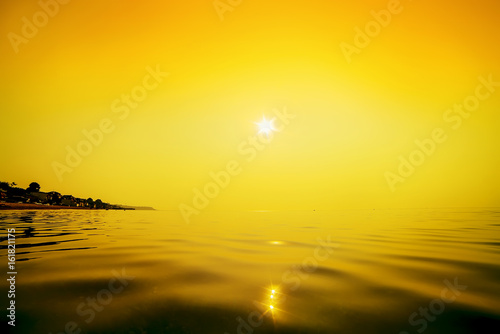 Fototapety, obrazy: Morning sea. View from the water to the houses on the shore. Calm orange water surface.