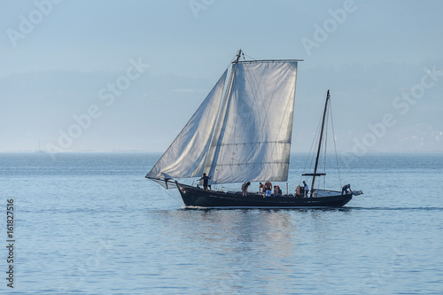sailing yacht sails against the sunset - Buy this stock photo and