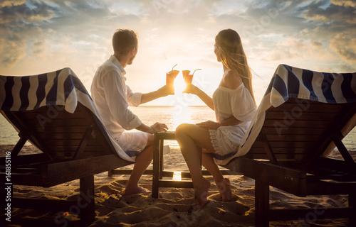Fotografering  Paar mit Cocktails am Strand auf Strandliegen schaut den Sonnenuntergang im Urla