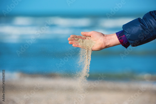 Photo  Young girl pouring sand from her hand