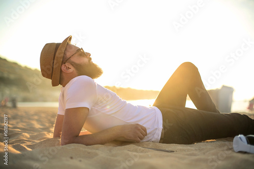 Handsome guy chilling at the beach Poster