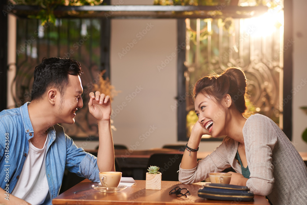Fototapety, obrazy: Side view portrait of laughing Asian couple enjoying date in cafe