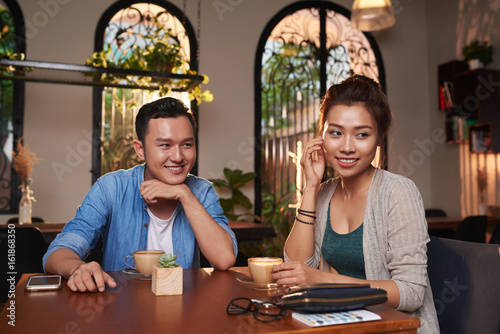 Obraz na plátně  Portrait of young Asian man flirting with beautiful woman in cafe