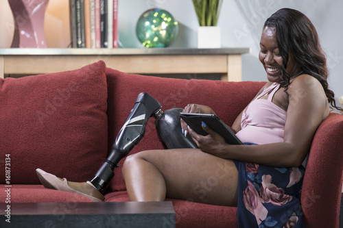 Black female amputee relaxing on a couch using a tablet Canvas Print