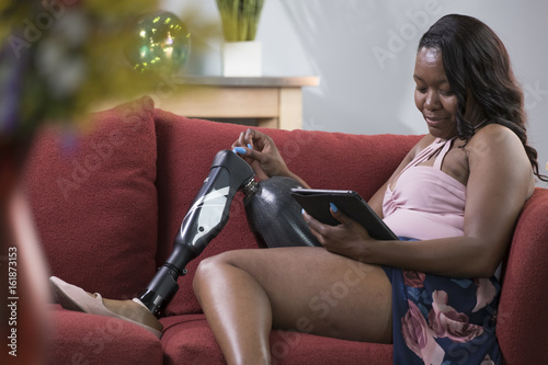 Valokuva  Black female amputee relaxing on a couch using a tablet