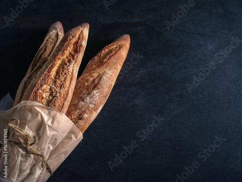 Fototapeta Three freshly baked baguettes on the table. obraz