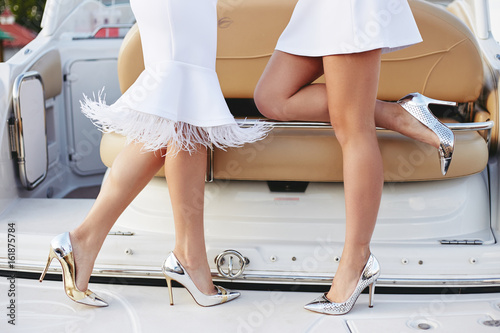 Fotografie, Obraz  Woman legs close up on silver shoes on yacht