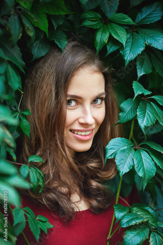 Portrait Of Beautiful Young Woman In Wild Leaves Grapes