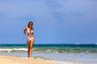 Model in white bikini walking at the beach