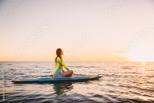 Plakat Wstań na pokładzie wiosłowania na spokojnym morzu w ciepłych kolorach zachodu słońca. Młoda kobieta jest relaksująca na oceanie
