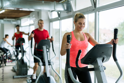 Poster Fitness People doing on elliptical trainer in gym