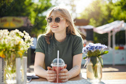 Young beautiful female student blogger taking a break from classes drinking grapefruit lemonade smiling looking left wearing glasses in park during a food festival on a sunny summer day Fototapeta