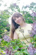 Beautiful blond girl in a lemon-yellow dress posing in lilac