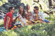 canvas print picture - Young people having picnic near the river. Young friends relaxing by the river