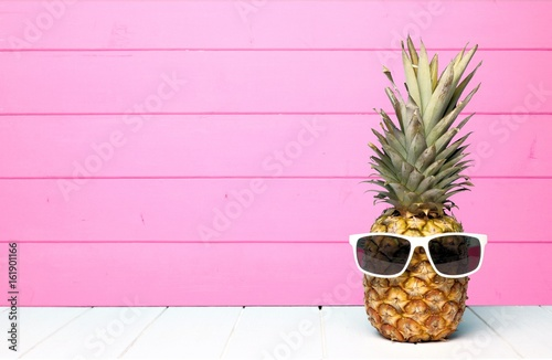 Photo Hipster pineapple with sunglasses against a pink wooden background
