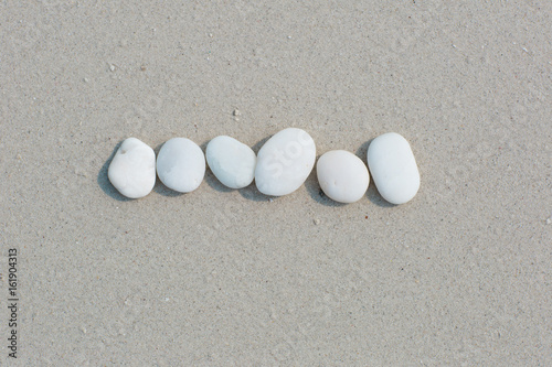 Photo sur Plexiglas Zen pierres a sable White pebbles, round small stones in a row on a wet white sand beach, space for letters or text