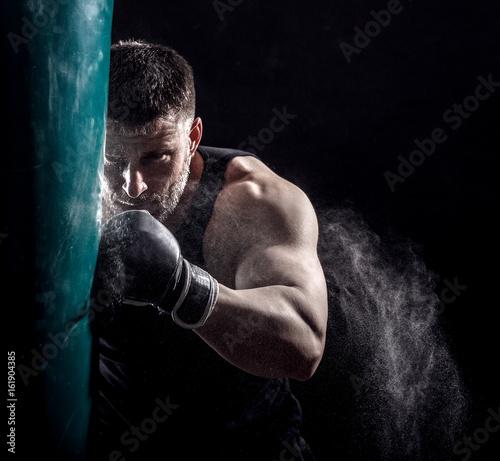 Studio shot of male boxer punching a boxing bag. Wallpaper Mural