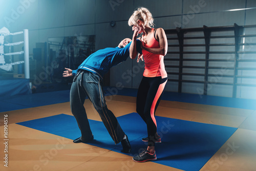 Photo Stands Martial arts Woman in actoin on self-defense training