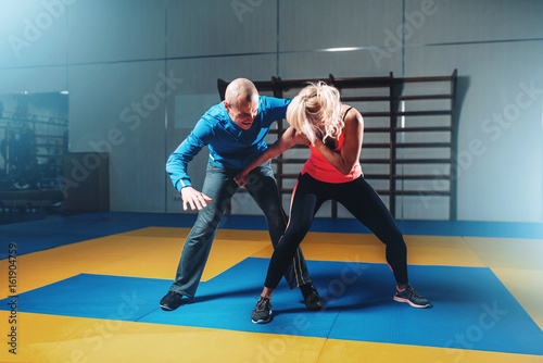 Photo Stands Martial arts Woman fights with man, self defense technique